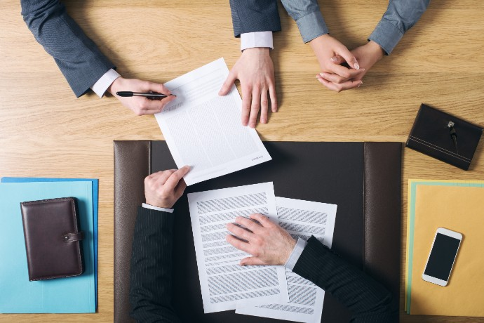 business-man-and-woman-sitting-at-the-lawyers-s-desk-and-signing-important-documents-hands-top-view